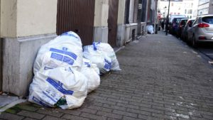 Little brown bag: White plastic rubbish bags in the street