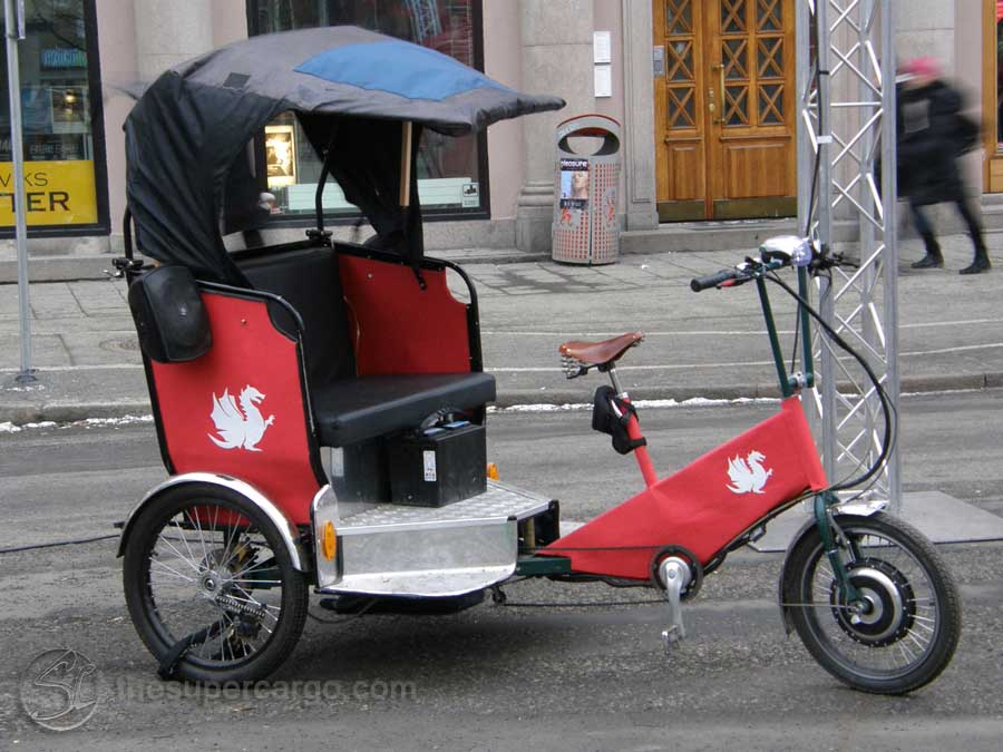 A pedal powered tricycle rickshaw with the dragon  logo of the Gothenburg International Film Festival parked outside the Pustervik temporary offices of the GIFF